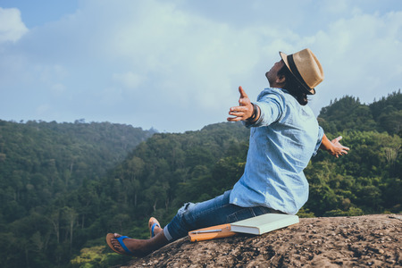 Photo for Asian man travel relax in the holiday. seats relax read books on rocky cliffs. On the Moutain. In Thailand - Royalty Free Image