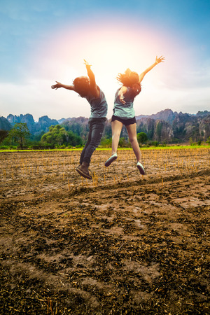 Foto de Asian men and women Lover jump travel relax. Rural landscape. Fields in season Natural rocky mountains - Imagen libre de derechos
