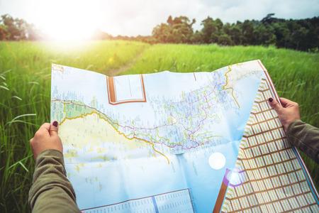 Photo pour woman  travel. Asian women's hand catches a map of travel Natural forest on the grassland - image libre de droit