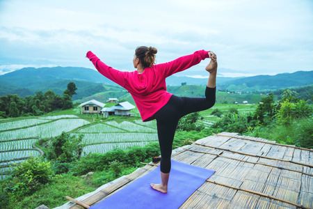 Foto de Asian woman relax in the holiday. Play if yoga. On the balcony landscape Natural Field.papongpieng in Thailand - Imagen libre de derechos