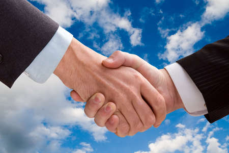 Two business men shaking hands on a background of the sky