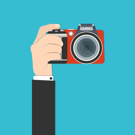 Ilustración de Vector illustration of a hand holding digital SLR camera for your design - Imagen libre de derechos