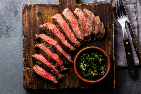Photo for Slices of beef medium rare steak on wooden board, glass of red wine on slate background - Royalty Free Image