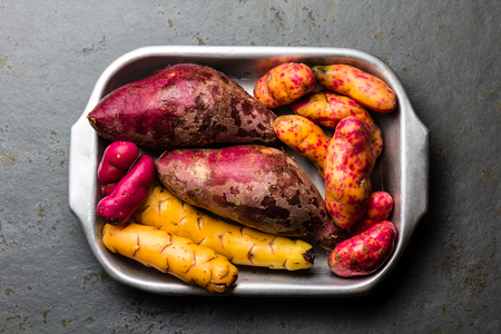 Foto de Peruvian raw ingredients for cooking - yuca, colored sweet potatoes and camote batata. Top view. - Imagen libre de derechos