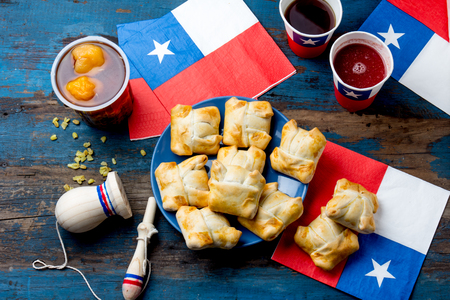 Foto per Chilean independence day concept. fiestas patrias. Chilean typical dish and drink on independence day party, 18 september. Mini empanadas, mote con huesillo, wine with toasted flour, chicha and tipical play emboque - Immagine Royalty Free