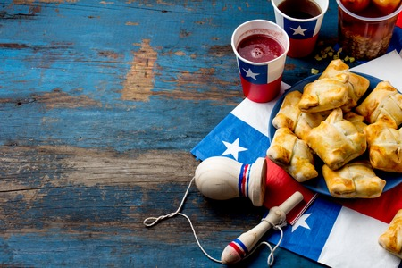 Foto de Chilean independence day concept. fiestas patrias. Chilean typical dish and drink on independence day party, 18 september. Mini empanadas, mote con huesillo, wine with toasted flour, chicha and tipical play emboque - Imagen libre de derechos