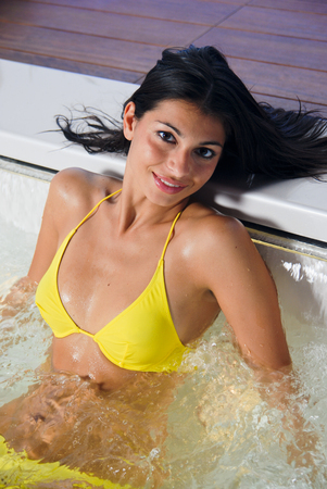 Foto de Young sexy brunette taking a hot tube hydromassage bath on a spa - Imagen libre de derechos