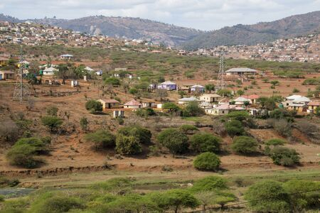 Foto de Housing and huts scattered informally over hills in rural south africa - Imagen libre de derechos