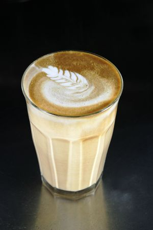 A double latte in a tall latte glass with latte art