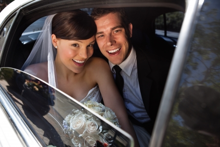 Foto de Portrait of happy newly wed couple in car - Imagen libre de derechos