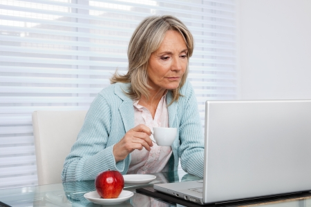 Photo for Mature woman working on laptop while holding cup of tea - Royalty Free Image