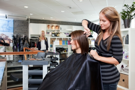 Hairdresser thinning customers hair in beauty salon