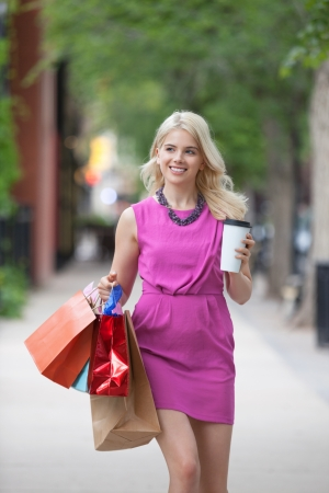 Happy young woman with shopping bags and disposable coffee cup on sidewalk