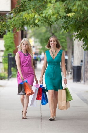Full length of young female friends with shopping bags walking on sidewalk