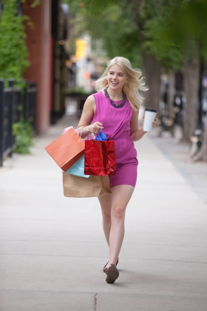 Pretty young woman with shopping bags and disposable coffee cup as she walks on sidewalk