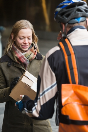 Young Woman Receiving A Package From Courier Delivery Man