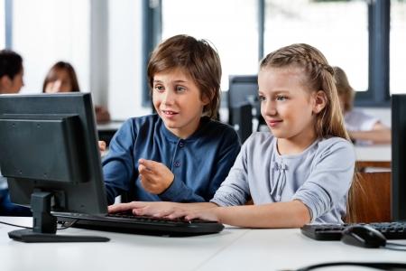Foto de Boy Pointing While Using Desktop Pc With Friend At Desk - Imagen libre de derechos