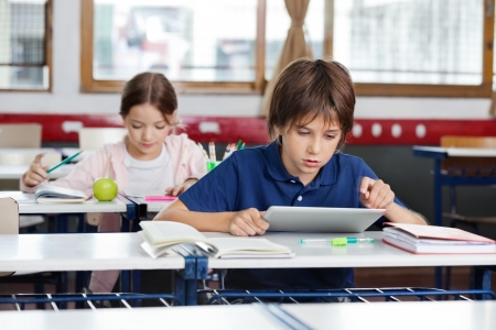 Photo pour Schoolboy Using Digital Tablet In Classroom - image libre de droit