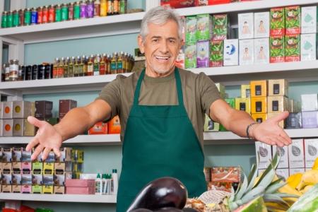 Photo pour Senior salesman with arms outstretched in supermarket - image libre de droit