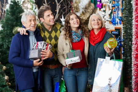Happy family with Christmas presents and bags shopping in store