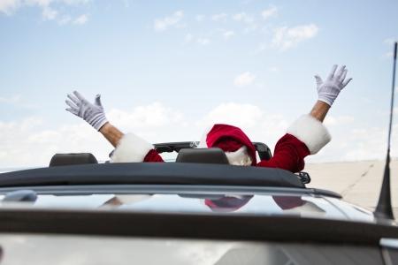 Photo pour Rear view of Santa with arms raised in convertible - image libre de droit