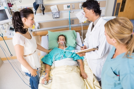 High angle view of young woman looking at doctor examining patient in hospital