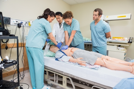 Foto de Female nurse performing CRP on dummy patient while doctor and colleagues looking at it in hospital room - Imagen libre de derechos
