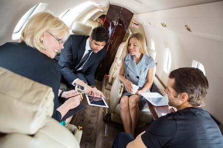 Foto de Businessman showing presentation on digital tablet with colleagues in corporate jet - Imagen libre de derechos