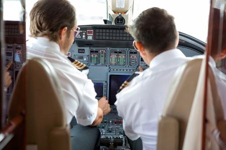 Photo pour Rear view of pilot and copilot operating controls of corporate jet - image libre de droit