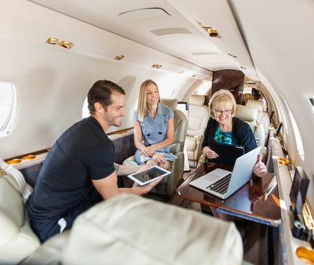 Foto de Business people having discussion over laptop on private jet - Imagen libre de derechos