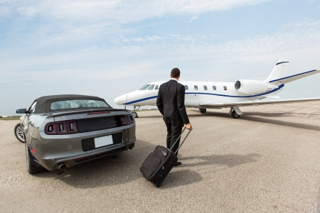 Foto de Businessman with luggage standing by car and private jet at airport terminal - Imagen libre de derechos