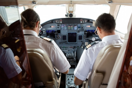 Photo pour Rear view of pilot and copilot in cockpit of private jet - image libre de droit