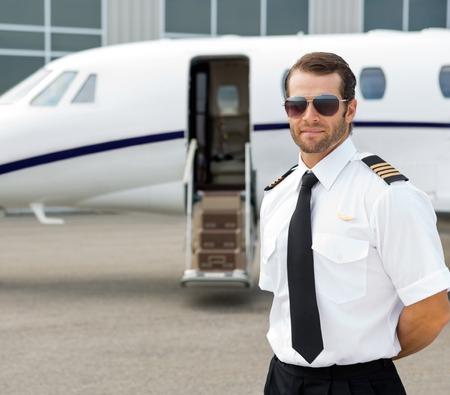 Photo pour Portrait of confident pilot wearing sunglasses with private jet in background - image libre de droit