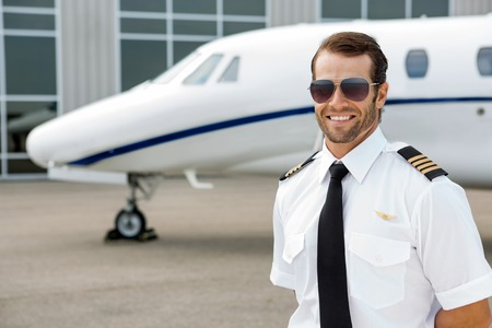 Photo pour Confident pilot smiling in front of private jet - image libre de droit