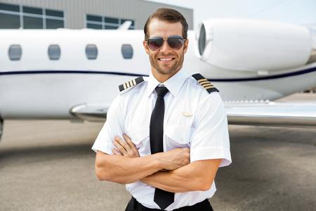 Photo pour Portrait of confident pilot smiling in front of private jet - image libre de droit