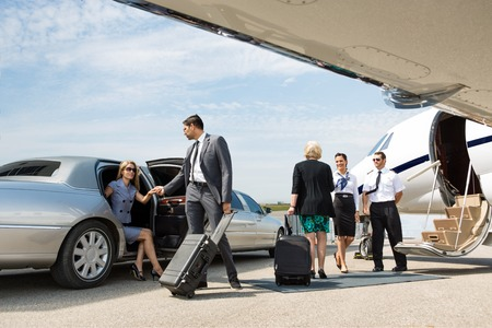 Photo pour Business partners about to board private jet while airhostess and pilot greeting them - image libre de droit