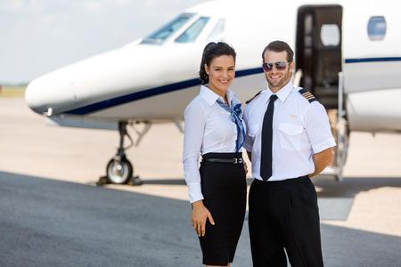 Photo pour Portrait of happy airhostess and pilot standing against private jet at terminal - image libre de droit