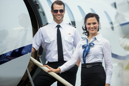 Photo pour Portrait of happy confident airhostess and pilot standing on private jet's ladder - image libre de droit