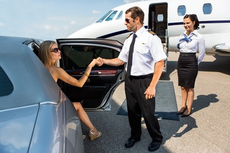 Photo pour Full length of pilot helping elegant woman stepping out of car at airport terminal - image libre de droit