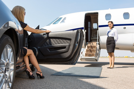 Photo pour Elegant woman stepping out of car parked in front of private plane and airhostess - image libre de droit