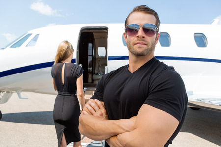 Foto de Confident bodyguard wearing sunglasses while standing against woman and private jet - Imagen libre de derechos