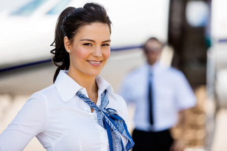 Photo pour Portrait of beautiful stewardesses smiling with pilot and private jet in background at terminal - image libre de droit