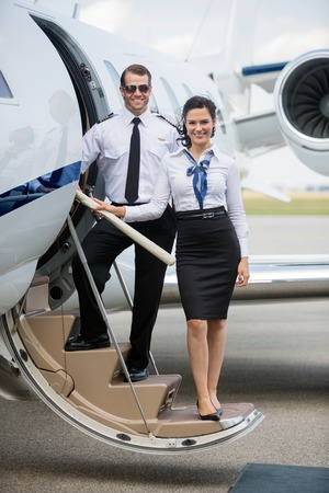 Photo pour Full length portrait of confident airhostess and pilot standing on ladder of private jet at airport terminal - image libre de droit