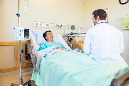 Smiling male patient looking at doctor while lying on bed in hospital room