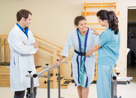 Photo for Female patient being assisted by physical therapists in hospital - Royalty Free Image