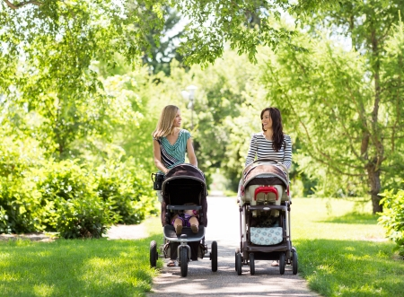 Photo for Happy mothers with their baby carriages walking together in park - Royalty Free Image