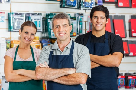 Photo pour Salespeople Standing Arms Crossed In Hardware Shop - image libre de droit