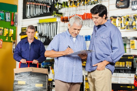 Foto de Customers Writing On Checklist In Hardware Store - Imagen libre de derechos
