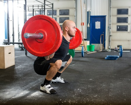 Foto de Male Athlete Lifting Barbell At Gym - Imagen libre de derechos