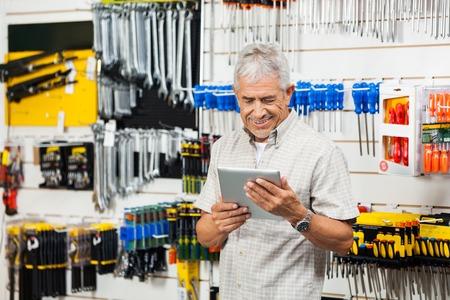 Foto für Customer Holding Digital Tablet In Hardware Shop - Lizenzfreies Bild